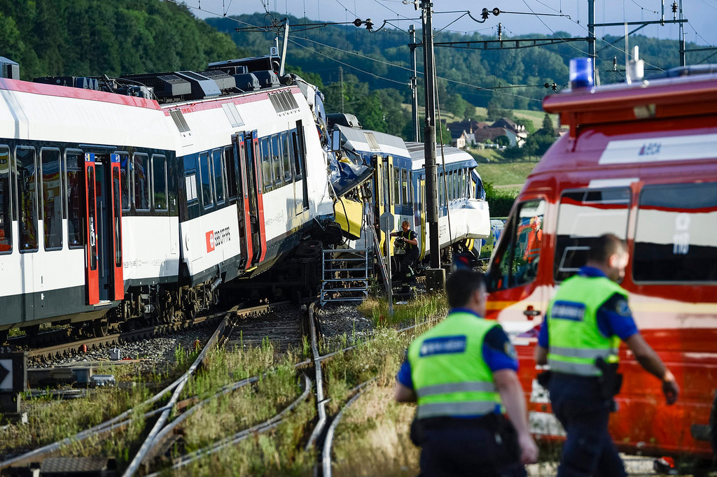 . Rescue personnel work at the site where two passenger trains collided head-on in Granges-pres-Marnand, western Switzerland, Monday, July 29, 2013. Numerous people have been injured.  (AP Photo/Keystone, Laurent Gillieron)