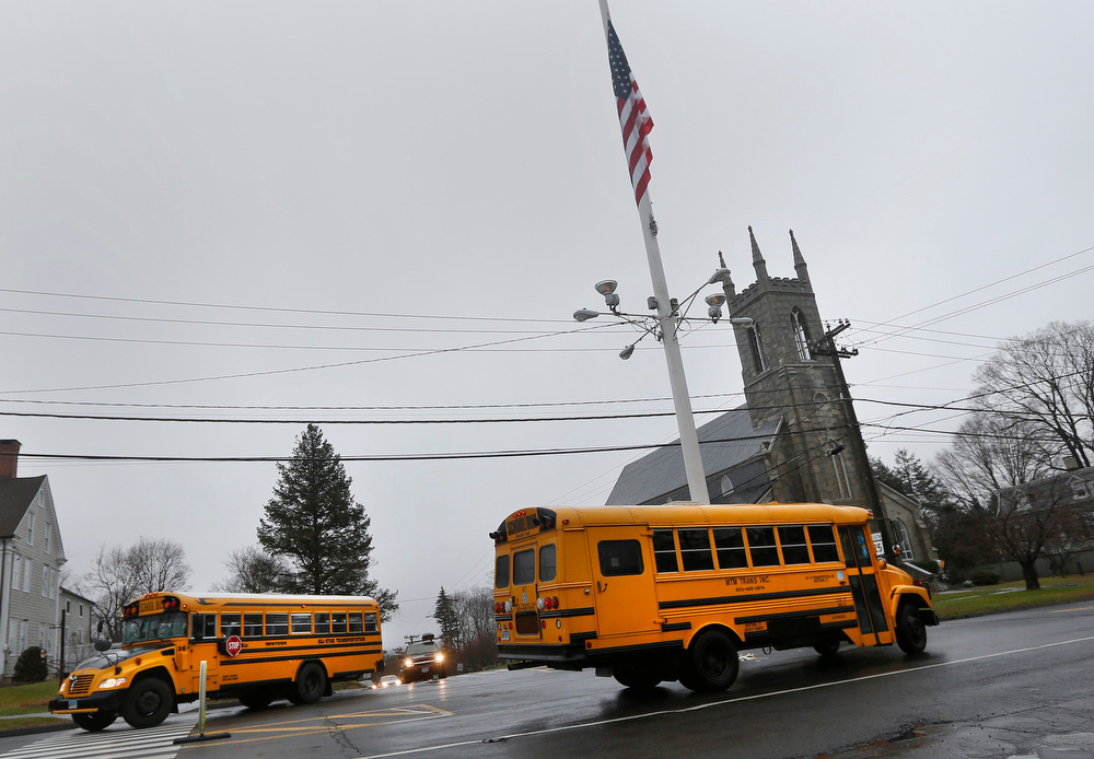 . School buses carrying students from the Newtown school district make their way past a flag at half-mast, down Main Street in Newtown, Connecticut December 18, 2012. The schools of Newtown, which stood empty in the wake of a shooting rampage that took 26 of their own at Sandy Hook Elementary, will again ring with the sounds of students and teachers on Tuesday as the bucolic Connecticut town struggles to return to normal.     REUTERS/Shannon Stapleton