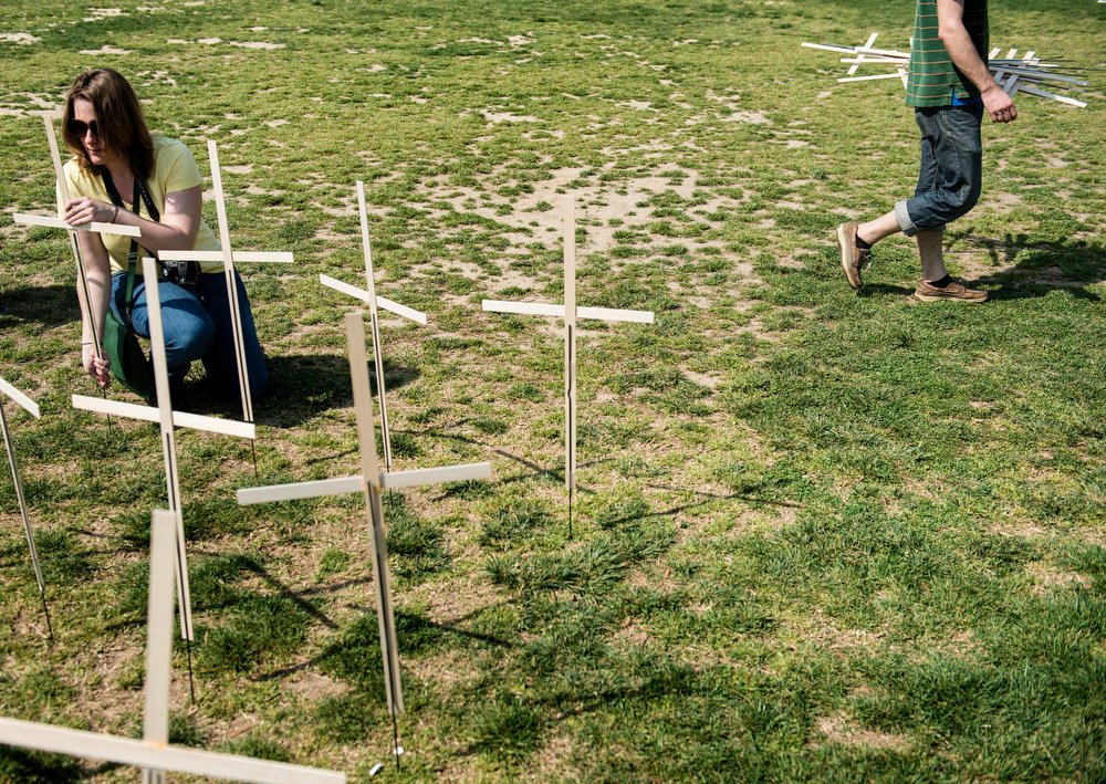 Description of . Activists place crosses on the National Mall for victims of gun violence April 11, 2013 in Washington, DC. The activists gathered to begin a 24 hour vigil on the National Mall with over 3,000 crosses for victims of gun violence in the United States since the Sandy Hook School shooting last December. BRENDAN SMIALOWSKI/AFP/Getty Images