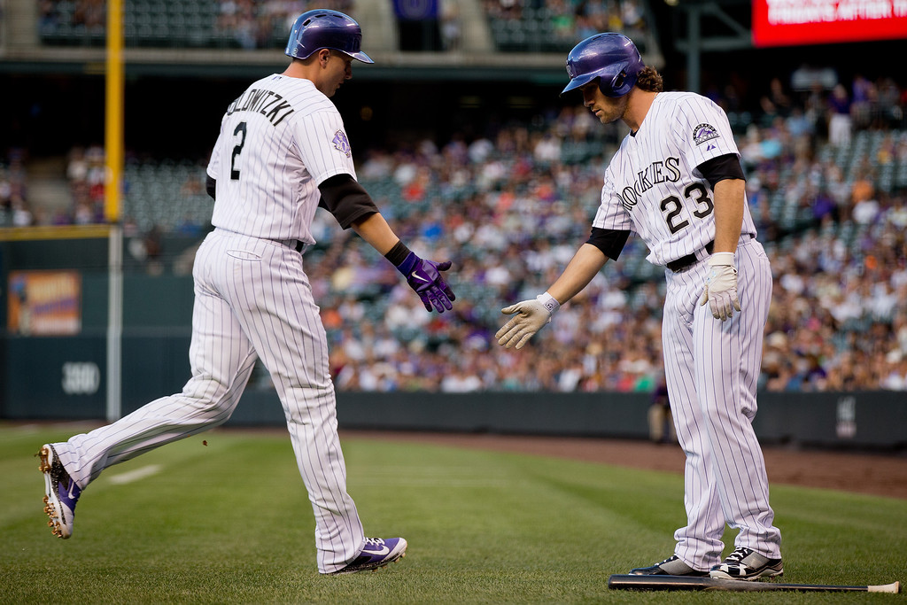 . Troy Tulowitzki #2 of the Colorado Rockies is congratulated by Charlie Culberson #23 after scoring during the first inning against the San Diego Padres at Coors Field on August 13, 2013 in Denver, Colorado.  (Photo by Justin Edmonds/Getty Images)