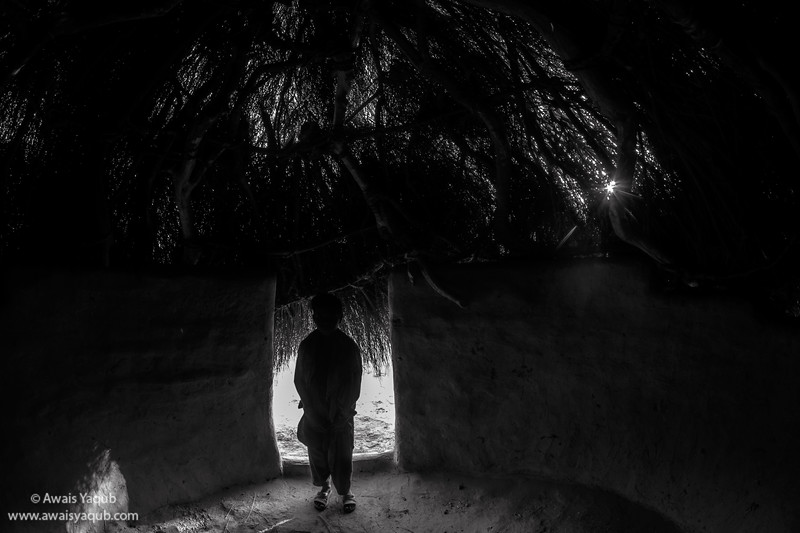 Boy stands in his hut