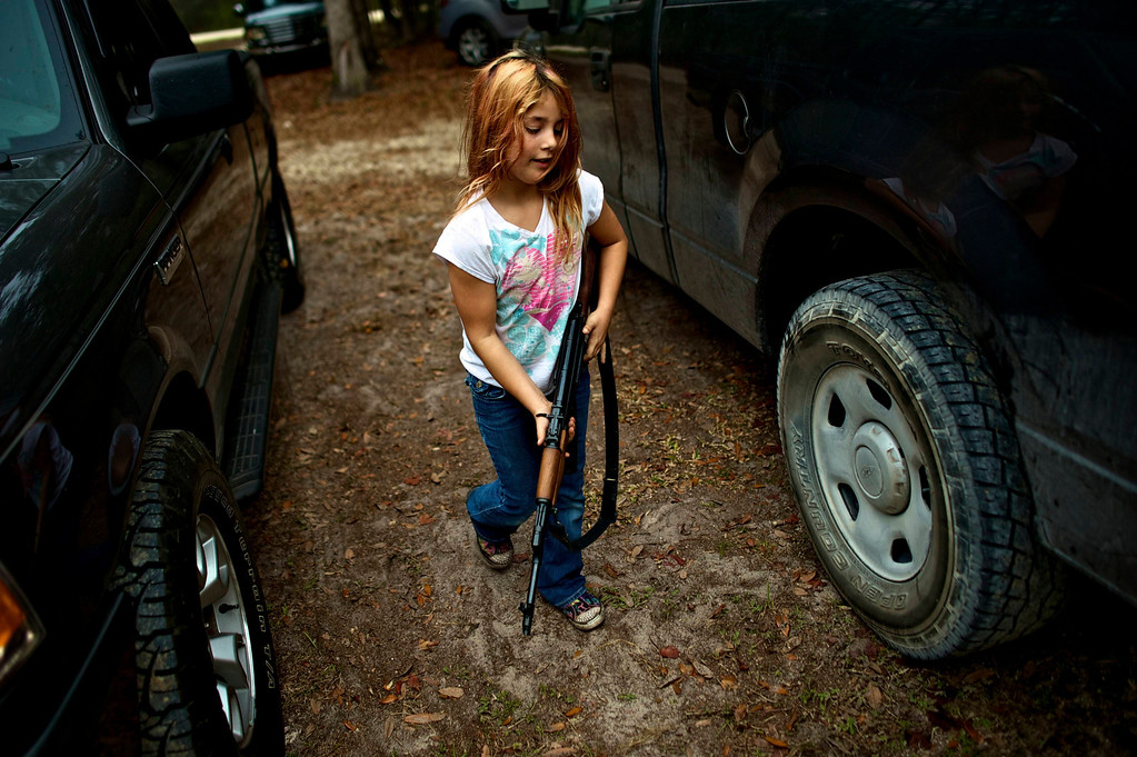 . Brianna, 9, of the North Florida Survival Group carries an AK-47 rifle from the group leader\'s truck before heading out to conduct enemy contact drills during a field training exercise in Old Town, Florida, December 8, 2012. REUTERS/Brian Blanco