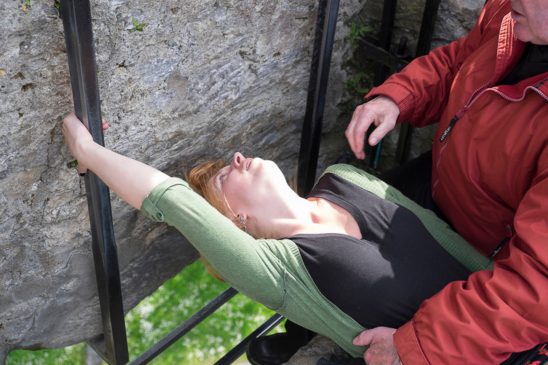 Molly being lowered to kiss the Blarney Stone.