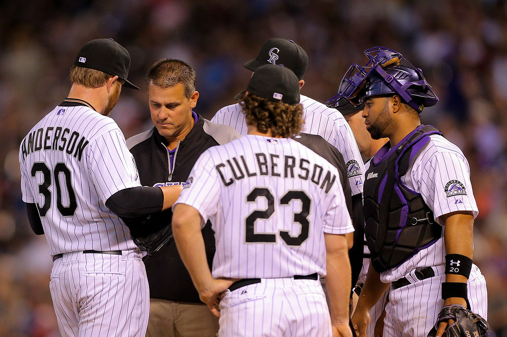 . Starting pitcher Brett Anderson #30 of the Colorado Rockies is checked out by the training staff and was removed from the game during the seventh inning against the Pittsburgh Pirates at Coors Field on July 25, 2014 in Denver, Colorado. (Photo by Justin Edmonds/Getty Images)