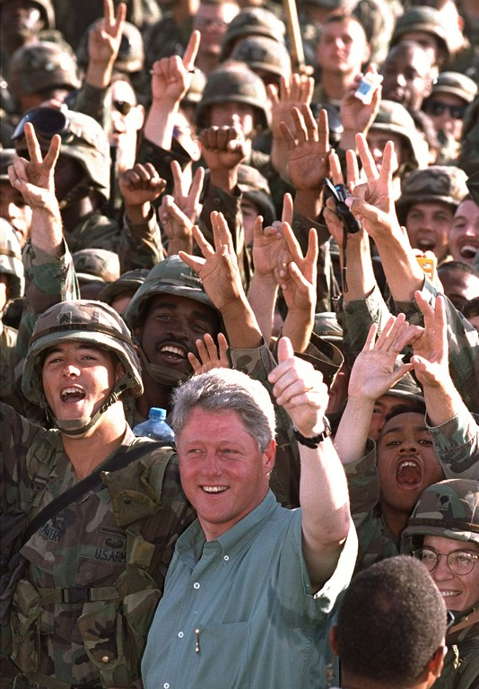 """. President Bill Clinton is cheered by U.S. soldiers with the first Brigade of the 24th Mechanized Infantry Division, of Fort Stewart, Ga., after addressing them at Tactical Assembly Area Liberty Friday Oct. 28, 1994 in Kuwait.  Facing the Iraqi border from the U.S. desert outpost President Clinton signaled his determination to deter any repeat of Saddam Hussein\'s 1990 invasion, \""""You are the steel and the sword of American diplomacy,\"""" he told American forces. (AP Photo/Marcy Nighswander)"""