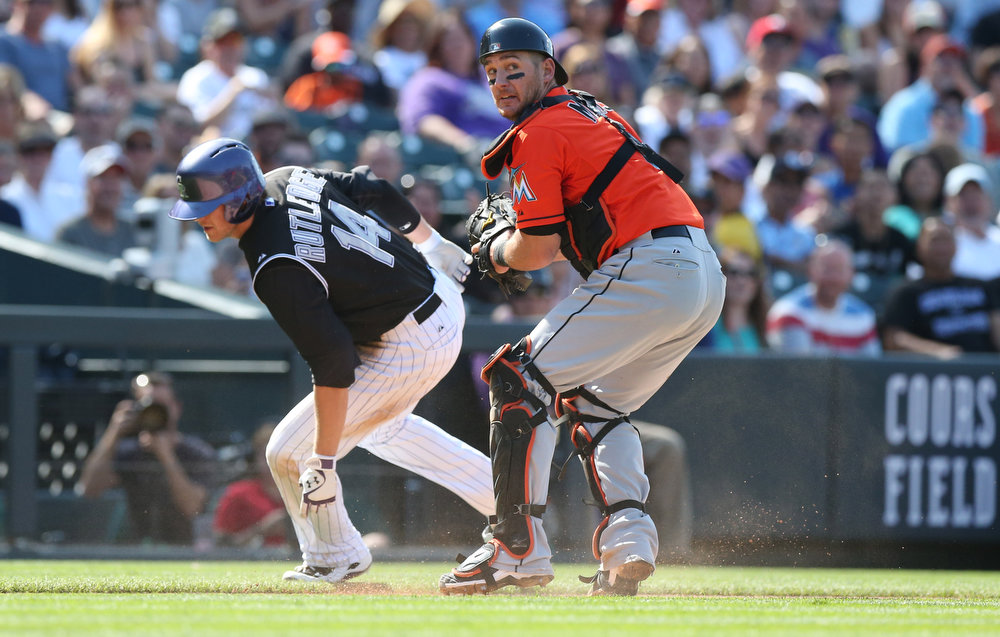 . Miami Marlins catcher Jeff Mathis, front, turns to check other runners after tagging out Colorado Rockies\' Josh Rutledge in a rundown between home plate and third base in the fourth inning of the Rockies\' 7-4 victory in a baseball game in Denver on Sunday, Aug. 24, 2014. (AP Photo/David Zalubowski)