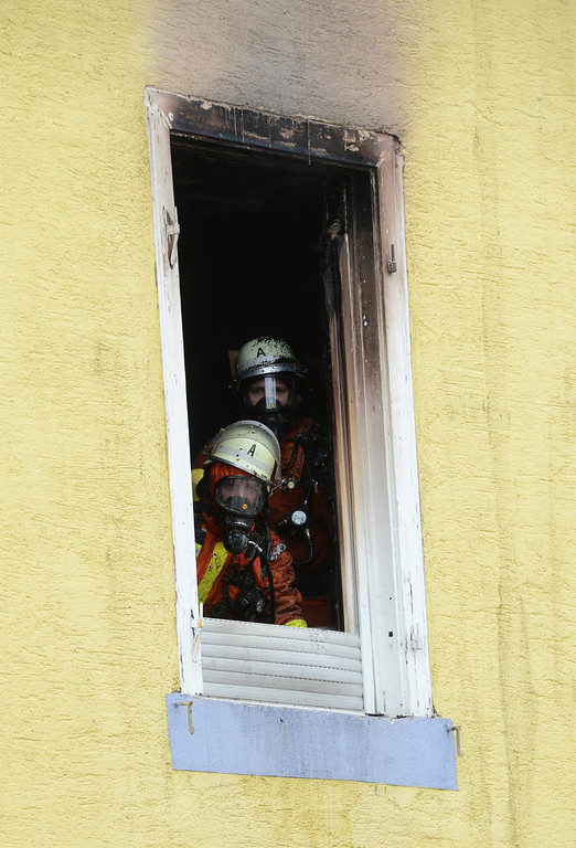 . Firefighters look out of the window of a house in  Backnang, Germany, Sunday March 10, 2013. An early-morning fire on Sunday at the apartment building in southwestern Germany left seven people dead, six of them children, police said. Authorities were alerted to the blaze in Backnang, a town near Stuttgart, at 4.30 a.m. Police said in a statement that they believe the fire broke out in a second-floor apartment, and said that their investigation is focusing on a heater in the apartment.   (AP Photo/dpa, Franziska Kraufmann)