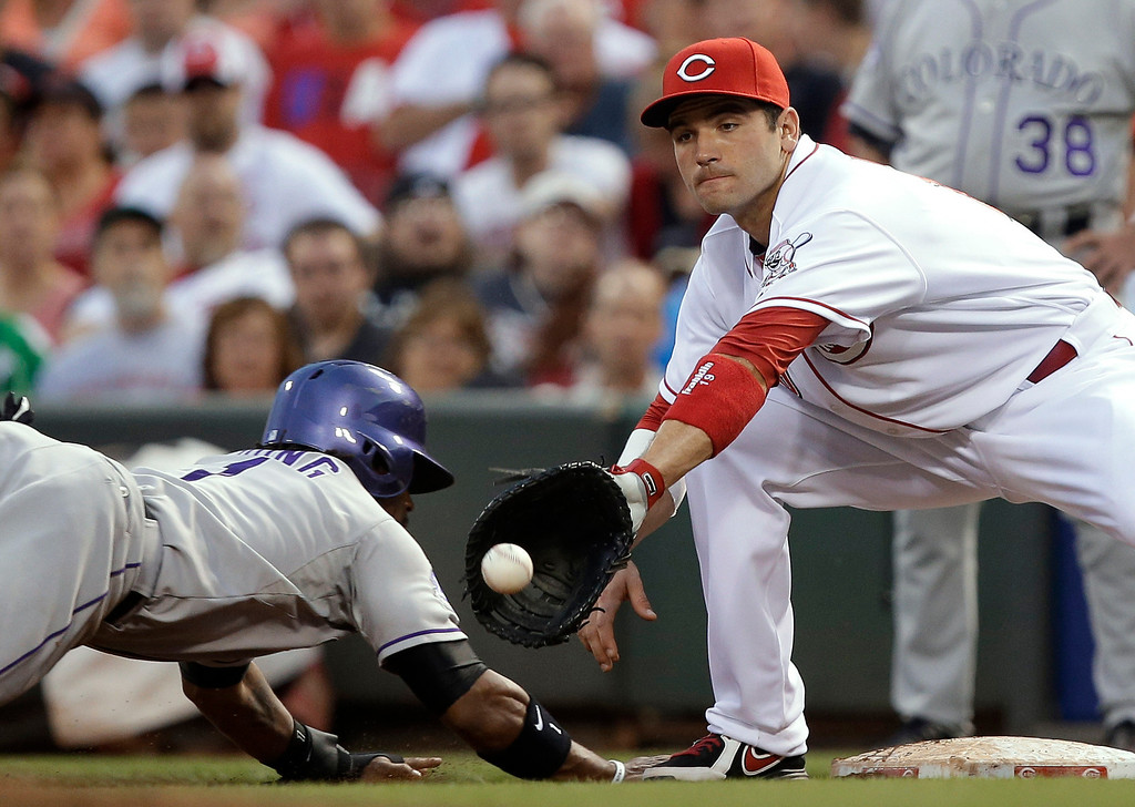. Colorado Rockies\' Eric Young Jr. (1) dives safely back to first as Cincinnati Reds first baseman Joey Votto catches a pickoff throw in the fourth inning of a baseball game, Wednesday, June 5, 2013, in Cincinnati. (AP Photo/Al Behrman)