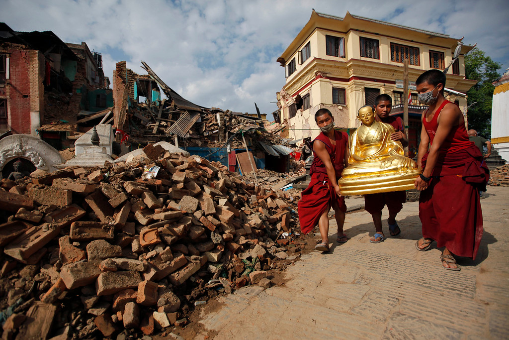 . Buddhist monks salvage a statue of a Buddhist deity from a monastery around the famous Swayambhunath stupa after it was damaged by Saturday\'s earthquake in  Kathmandu, Nepal, Thursday, April 30, 2015. In mere seconds, Saturday\'s earthquake devastated a swathe of Nepal. Three of the seven World Heritage sites in the Kathmandu Valley have been severely damaged, including Durbar Square with pagodas and temples dating from the 15th to 18th centuries, according to UNESCO, the United Nations cultural agency. (AP Photo/Niranjan Shrestha)