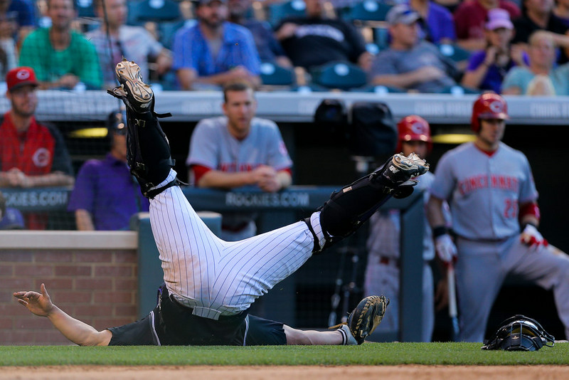 . Catcher Michael McKenry #8 of the Colorado Rockies falls to the ground trying to catch an errant throw from the outfield during the eighth inning against the Cincinnati Reds at Coors Field on August 17, 2014 in Denver, Colorado. The Rockies defeated the Reds 10-9. (Photo by Justin Edmonds/Getty Images)