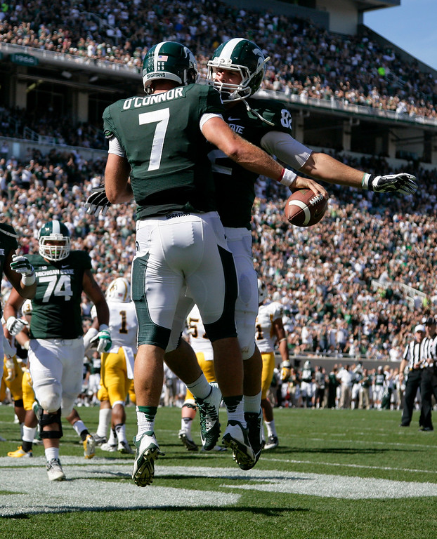 . Michigan State\'s Tyler O\'Connor (7) and Josiah Price celebrate O\'Connor\'s touchdown during the fourth quarter of an NCAA college football game against Wyoming, Saturday, Sept. 27, 2014, in East Lansing, Mich. Michigan State won 56-14. (AP Photo/Al Goldis)