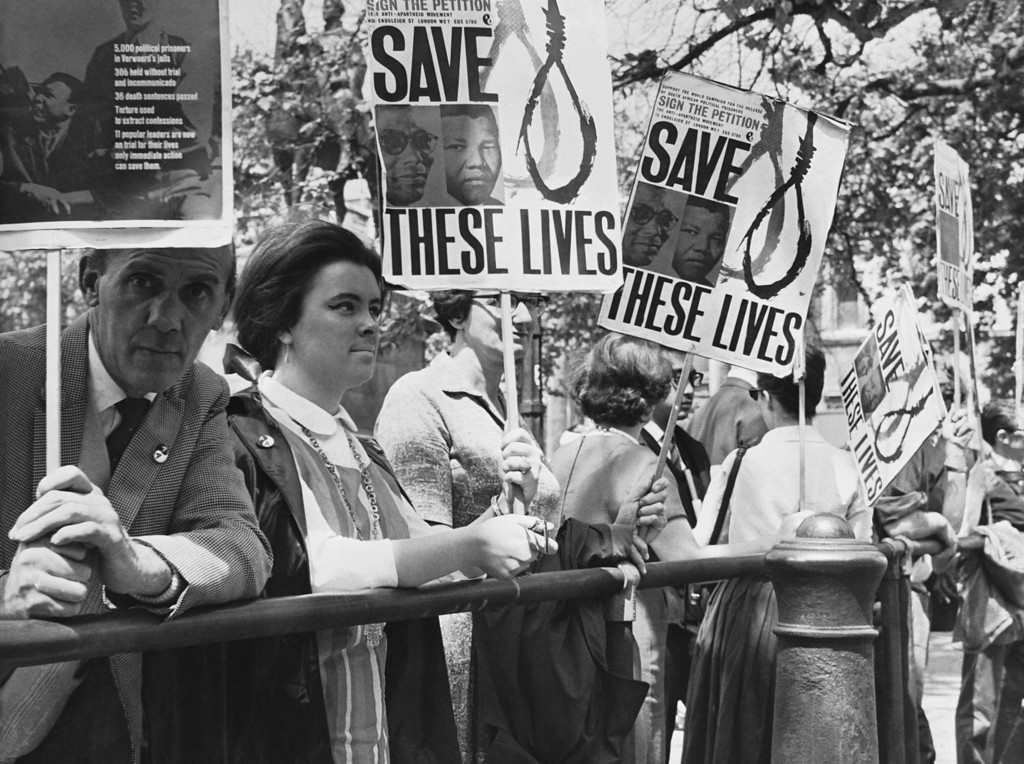 . Anti-apartheid demonstrators gather outside the South African Embassy in Trafalgar Square, London, June 12, 1964, in protest against the sentence to life imprisonment of Nelson Mandela, former chief of the banned African National Congress. Mandela, 46, and seven other defendants were found guilty in the South African treason trial in Pretoria. They were sentenced today. (AP Photo)