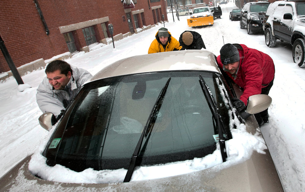 . A group of men help push a sports car up a snow-covered street in the Old Port section of Portland, Maine, during a snow storm, Friday, Feb. 8, 2013. The storm is expected to dump up to two feet of snow on the region. (AP Photo/Robert F. Bukaty)