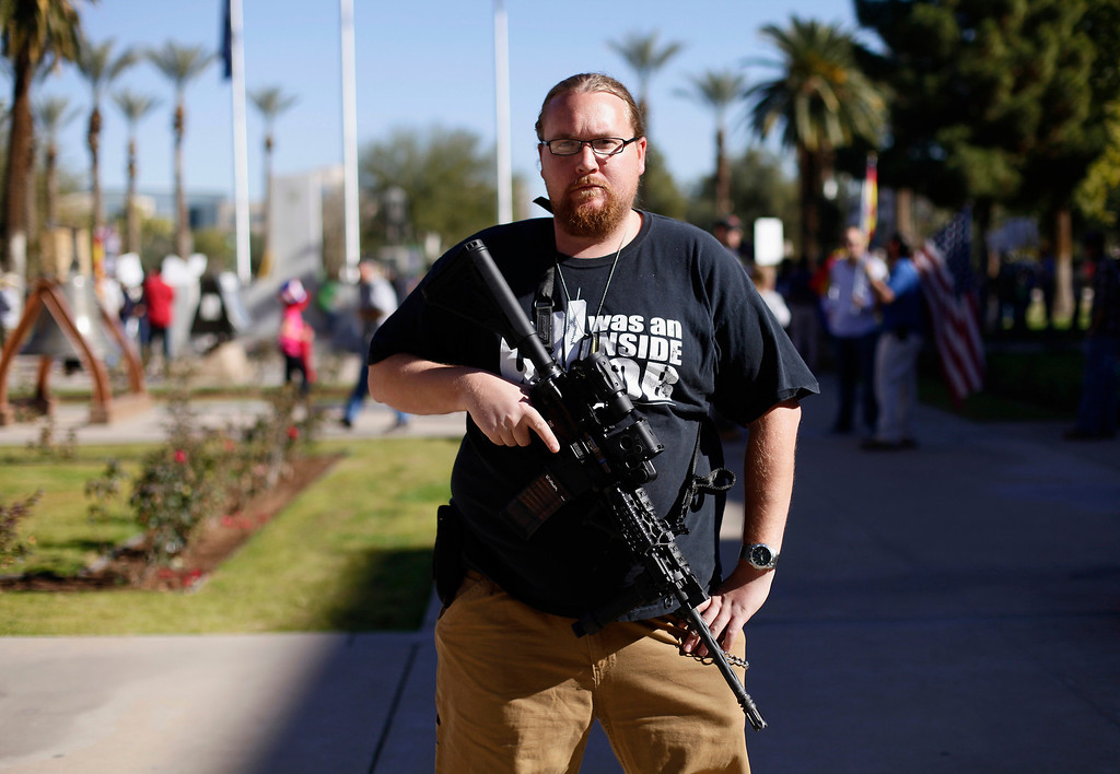 ". Brandon Smith poses with his AR-15 rifle during a pro-gun and Second Amendment protest outside the Arizona State Capitol in Phoenix, Arizona January 19, 2013. Pro-gun activists held ""high noon\"" rallies across the United States to defend the right to own firearms that they say is being threatened by U.S. President Barack Obama\'s gun-control proposals. REUTERS/Joshua Lott"