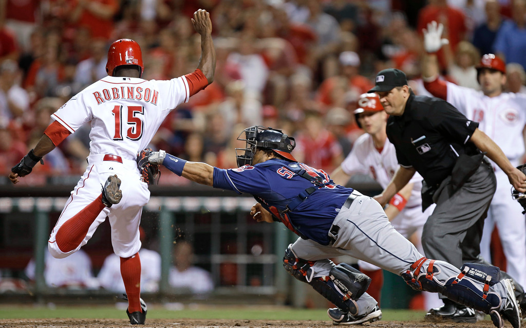. Cleveland Indians catcher Carlos Santana tags Cincinnati Reds\' Derrick Robinson (15) out at home in the seventh inning of a baseball game, Tuesday, May 28, 2013, in Cincinnati. Robinson was trying to score on a hit by Zack Cozart. (AP Photo/Al Behrman)