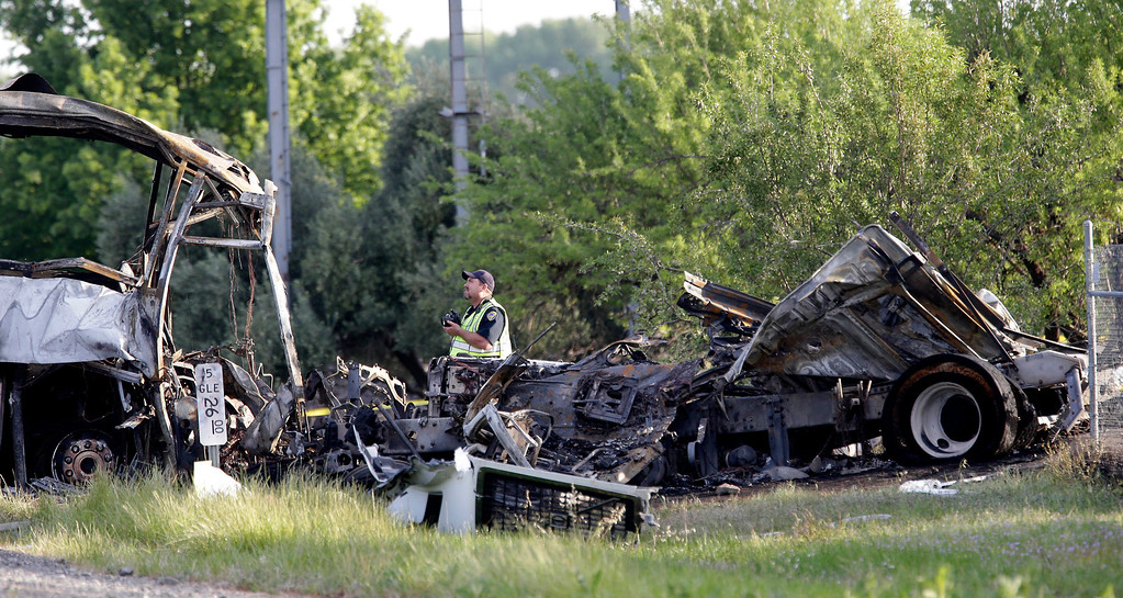 . A California Highway Patrol Officer looks over  the wreckage, Friday, April 11, 2014, where a tour bus and a FedEX truck crashed on Interstate 5 Thursday in Orland, Calif.  At least ten people were killed and dozens injured in the fiery crash between the truck and a bus carrying high school students on a visit to a Northern California College.(AP Photo/Rich Pedroncelli)