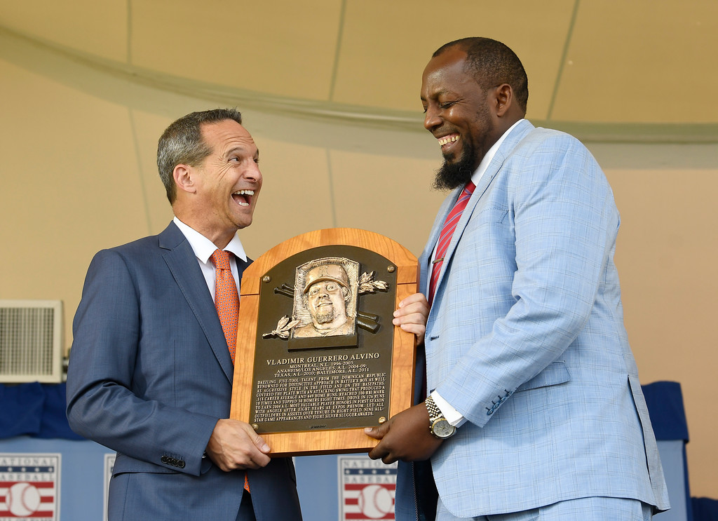 . Hall of Fame President Jeff Idelson, left, poses with Vladimir Guerrero during an induction ceremony at the Clark Sports Center on Sunday, July 29, 2018, in Cooperstown, N.Y. (AP Photo/Hans Pennink)