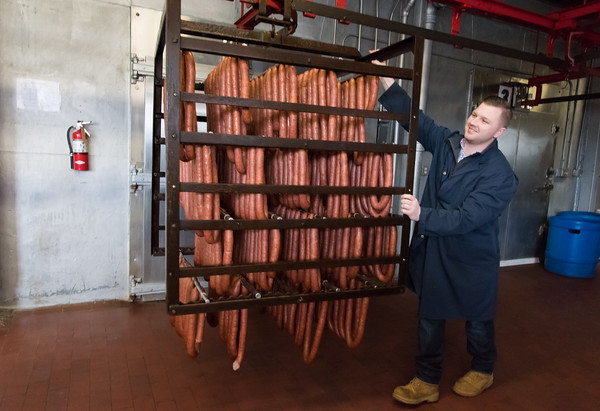 03/27/18 Wesley Bunnell | Staff General Manager Ted Rosol pushes a rack of 300 pounds of their special easter smoked kielbasa on Tuesday afternoon into a drying room. In the month leading up to Easter Rosols with sell 100,000 pounds of the special easter smoked and 25,000 pounds of the fresh kielbasa.