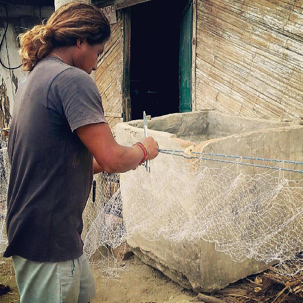 A_familiar_site_in_Canoa__Jairon_is_fixingrestitching_his_fishing_net.__Crabs_or_other_fish_become_too_entangled_and_while_the_fishermen_try_to_untangle_them__sometimes_they_need_to_be_ripped_out_also_tearing_the_net..jpg