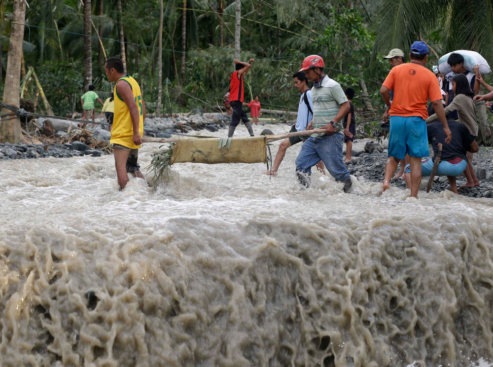 Description of . Residents cross a river with the body of a child after retrieving it from the flash flood-hit village of Andap, in New Bataan township, Compostela Valley in southern Philippines Wednesday Dec. 5, 2012, a day after the devastating Typhoon Bopha made landfall. Typhoon Bopha, one of the strongest typhoons to hit the Philippines this year, barreled across the country\'s south on Tuesday, killing scores of people while triggering landslides, flooding and cutting off power in two entire provinces. (AP Photo/Bullit Marquez)
