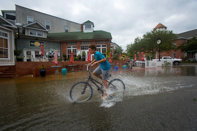 . Bryson Casey splashes through the flooded street after a a storm, Friday, July 4, 2014, in Manteo, N.C. The storm was expected to bring a lousy July Fourth beach day with it as it moved offshore of the northeast coast. Forecasters did predict a second landfall Saturday evening in New Brunswick and Nova Scotia in Canada. (AP Photo/The Virginian-Pilot, Hyunsoo Leo Kim)