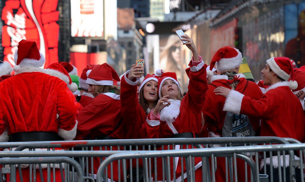 . People dressed as Santa Claus and Mrs. Claus take selfies in Times Square as they gather for the annual Santacon festivities on December 13, 2014 in New York. AFP PHOTO/DON  EMMERT/AFP/Getty Images