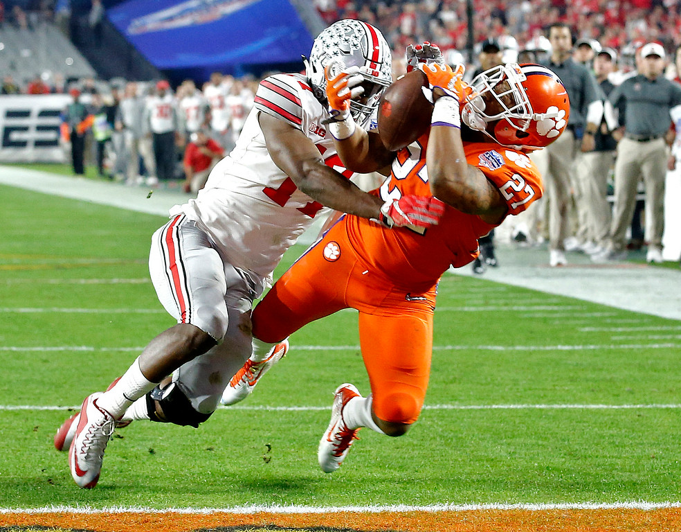 . Clemson running back C.J. Fuller (27) makes a touchdown catch as Ohio State cornerback C.J. Saunders (17) defends during the first half of the Fiesta Bowl NCAA college football playoff semifinal, Saturday, Dec. 31, 2016, in Glendale, Ariz. (AP Photo/Ross D. Franklin)