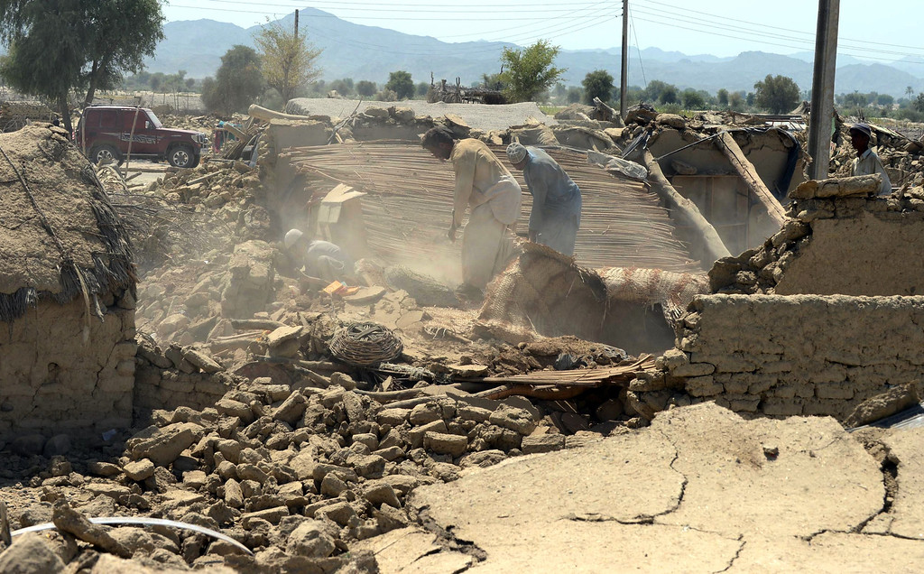 . Pakistani earthquake survivors remove debris from their collapsed mud houses in the earthquake-devastated district of Awaran on September 25, 2013.  AFP PHOTO/Banaras KHAN/AFP/Getty Images