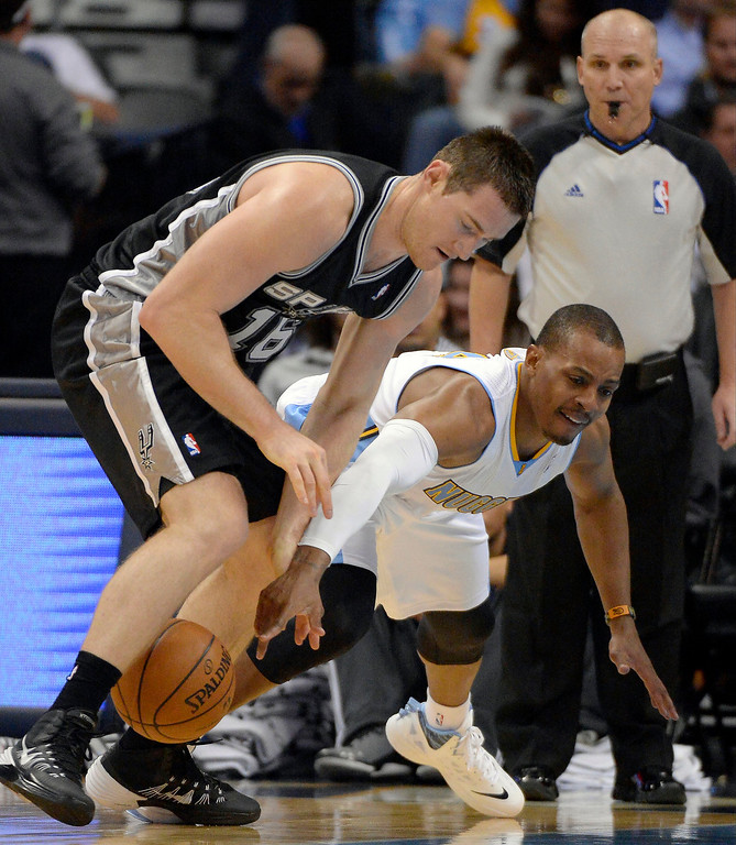 . DENVER, CO - OCTOBER 14: Denver Nuggets point guard Randy Foye (4) reaches for the ball as it bounces between the legs of San Antonio Spurs power forward Aron Baynes (16) October 14, 2013 at Pepsi Center. (Photo By John Leyba/The Denver Post)