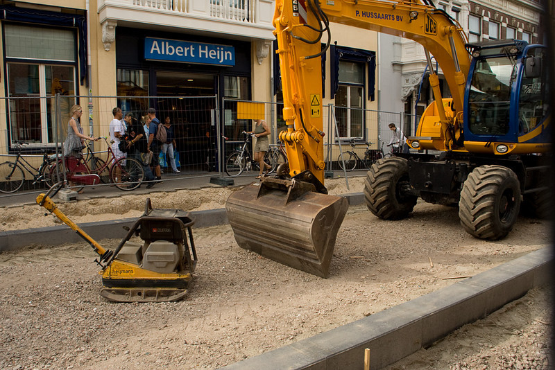 Big and little machinery. Holly likes backhoes, ever since we rented a little one to dig a trench around our house for drainage.  The Albert Heijn you see in the back is a grocery store chain we went to all the time.