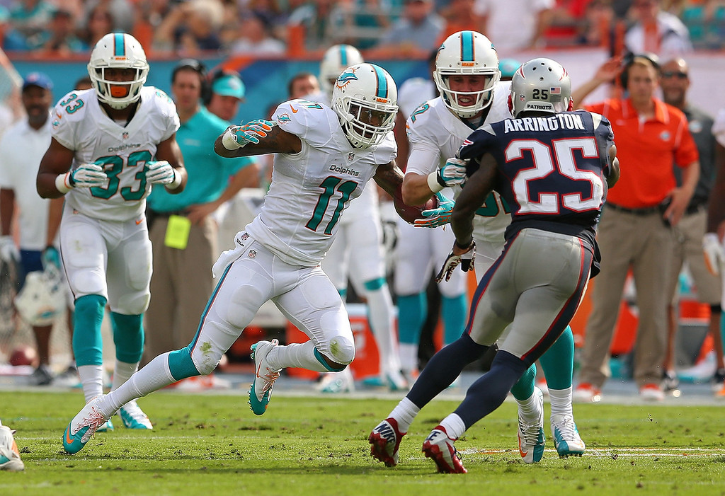 . Mike Wallace #11 of the Miami Dolphins makes a catch in front of Kyle Arrington #25 of the New England Patriots during a game  at Sun Life Stadium on December 15, 2013 in Miami Gardens, Florida.  (Photo by Mike Ehrmann/Getty Images)