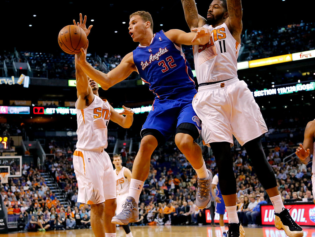 . Los Angeles Clippers forward Blake Griffin (32) passes under pressure from Phoenix Suns forward Markieff Morris (11) during the first half of an NBA basketball game on Wednesday, April 2, 2014,in Phoenix. (AP Photo/Matt York)