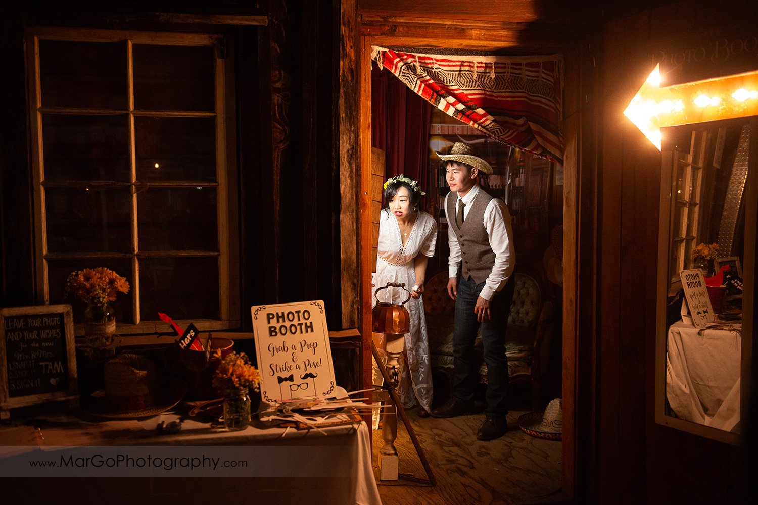 bride and groom at photo booth during wedding reception at Long Branch Saloon & Farms in Half Moon Bay