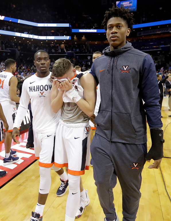 . Virginia\'s Kyle Guy, center, walks off the court following the team\'s 74-54 loss to UMBC in a first-round game in the NCAA men\'s college basketball tournament in Charlotte, N.C., Friday, March 16, 2018. (AP Photo/Gerry Broome)