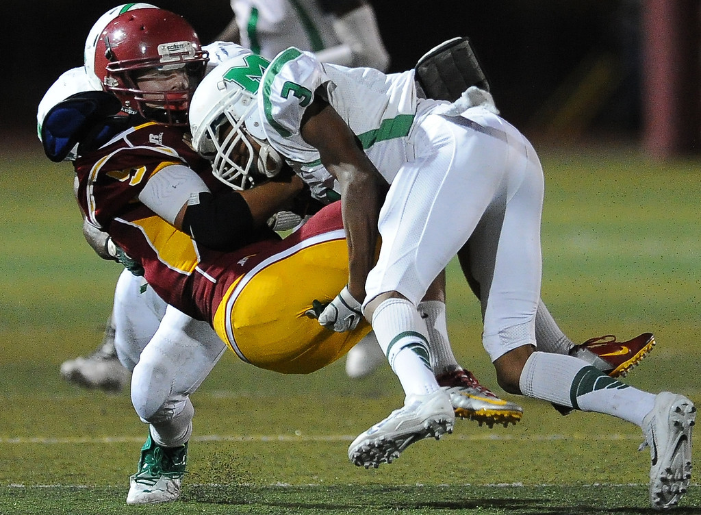 . Arcadia\'s Joe Haines (9) is his hard by Monrovia\'s Darius McClain (3) in the first half of a prep football game at Arcadia High School in Arcadia, Calif. on Friday, Sept. 13, 2013.   (Photo by Keith Birmingham/Pasadena Star-News)