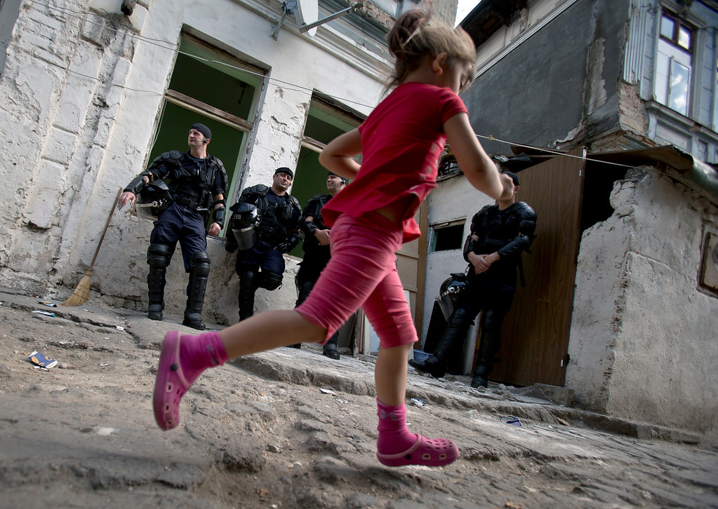 . A Roma child runs by riot policemen whilst more than 100 people are evicted from the homes they lived in, in Bucharest, Romania, Monday, Sept. 15, 2014. (AP Photo/Vadim Ghirda)