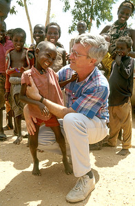A smiling African child being held by a medical volunteer.  Photo by Jim Whitmer