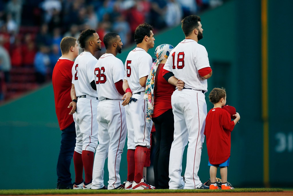 . Boston Red Sox\'s Xander Bogaerts (2), Eduardo Nunez (36), Ian Kinsler (5) and Mitch Moreland (18) stand with cancer patients during the national anthem before a baseball game against the Cleveland Indians in Boston, Tuesday, Aug. 21, 2018. (AP Photo/Michael Dwyer)