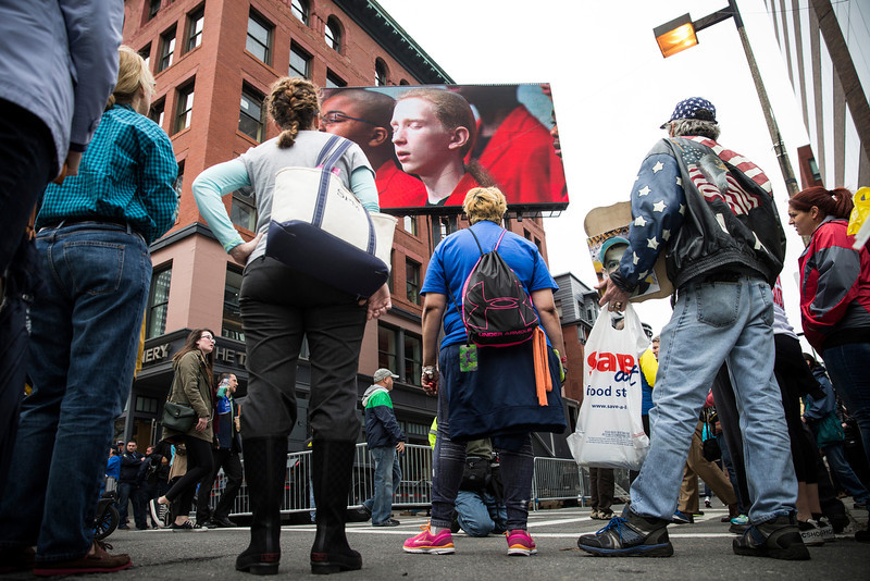 . People watch a billboard television screen broadcasting the ceremony commemorating the one year anniversary of the 2013 Boston Marathon Bombing , on April 15, 2014 in Boston, Massachusetts. Last year, two pressure cooker bombs killed three and injured an estimated 264 others during the Boston marathon, on April 15, 2013. Neary says she was standing near the site of the bombing before it went off.  (Photo by Andrew Burton/Getty Images)