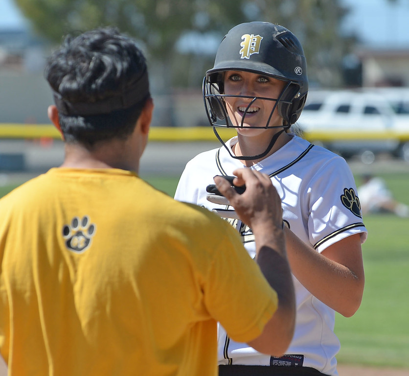 . Peninsula assistant coach Roman Hernandez cheers Katie Holcomb after her hustle got her to first against Arroyo Grande in a CIF Southern Section Division III wild-card softball game in Rolling Hills Estates Tuesday. Peninsula won the game 13-0. 20130514 Photo by Steve McCrank / Staff Photographer