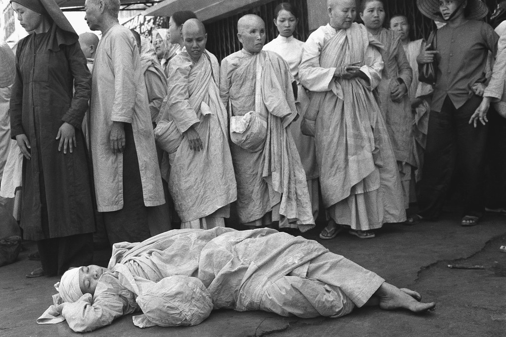 . South Vietnamese Buddhist nun injured in melee between police and about 20 nuns staging demonstration rests on floor at pagoda surrounded by other activist religious in Saigon, Sunday, Jan. 26, 1975. Antigovernment protest and fighting followed political convention. Four nuns were injured, none of them seriously. (AP Photo/Nguyen Tu A)