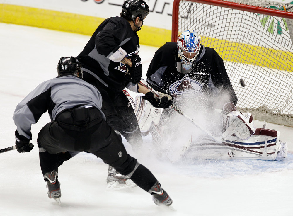 . Colorado Avalanche goalie Jean-Sebastien Giguere attempts to block a shot during NHL hockey practice, Thursday Jan. 17, 2013, in Denver, Colo. (AP Photo/Brennan Linsley)