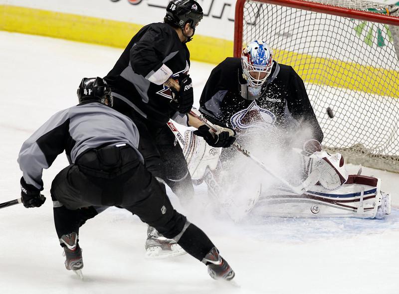 . Colorado Avalanche goalie Jean-Sebastien Giguere attempts to block a shot during NHL hockey practice, Thursday Jan. 17, 2013, in Denver, Colo. (AP Photo/Brennan Linsley)
