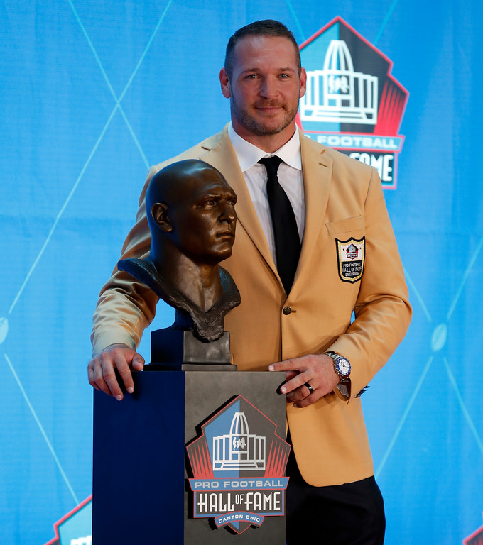 . Former NFL player Brian Urlacher poses with a bust of himself during an induction ceremony at the Pro Football Hall of Fame Saturday, Aug. 4, 2018, in Canton, Ohio. (AP Photo/Ron Schwane)