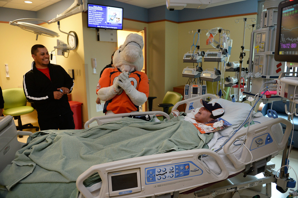 . Emmanuel Vargas, 11, laughs with Miles, the Broncos Mascot, as he made a surprise visit to him in his room in the Pediatric Intensive Care Unit at the  Rocky Mountain Hospital for Children in Denver, Co on January 14, 2014.   (Photo By Helen H. Richardson/ The Denver Post)