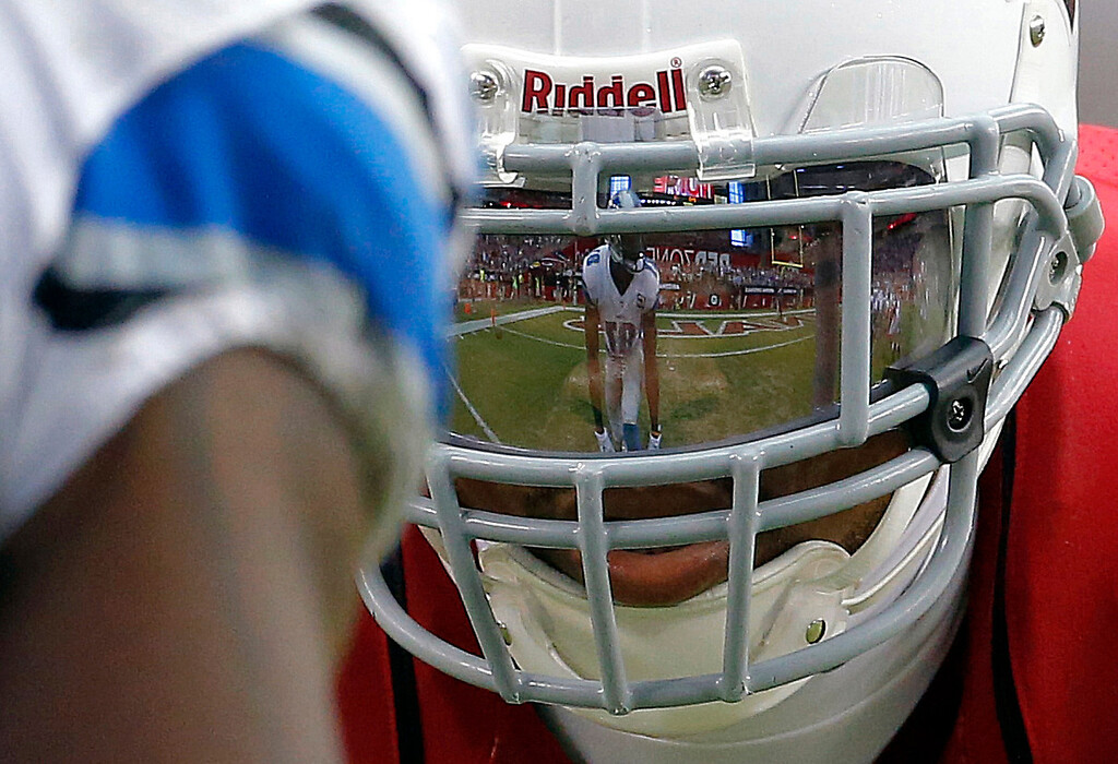 . Detroit Lions wide receiver Calvin Johnson is reflected in the face mask of Arizona Cardinals defensive back Patrick Peterson during the second half of a NFL football game, Sunday, Sept. 15, 2013, in Glendale, Ariz. (AP Photo/Darryl Webb)