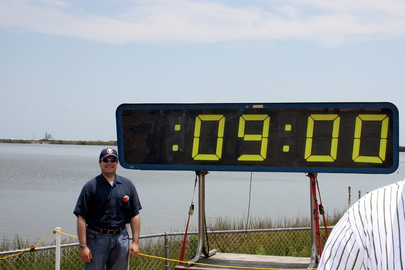 Craig with the countdown clock holding at T minus 9 minutes to liftoff, with Space Shuttle Atlantis on Launch Pad 39-A in the background