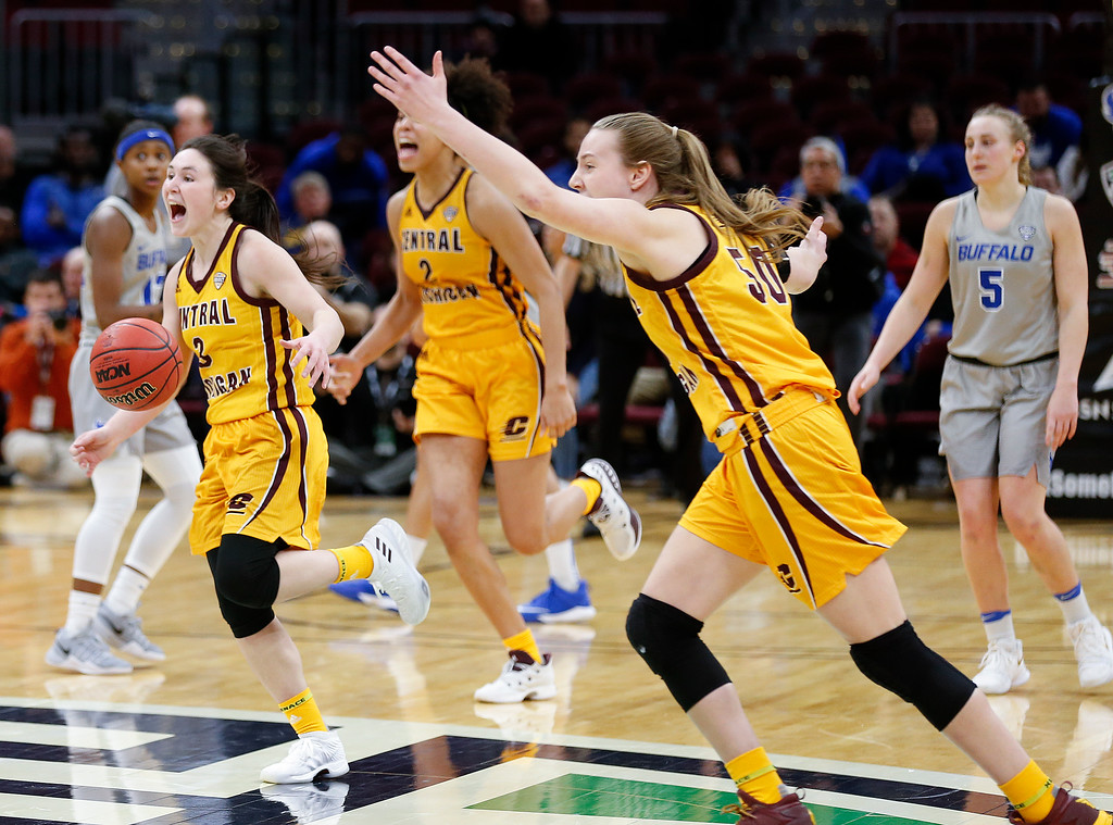 . Central Michigan guard Presley Hudson (3), Tinara Moore (2) and Kyra Bussell (50) celebrate after defeating Buffalo 96-91 in an NCAA college basketball game in the championship of the Mid-American Conference tournament Saturday, March 10, 2018, in Cleveland. (AP Photo/Ron Schwane)