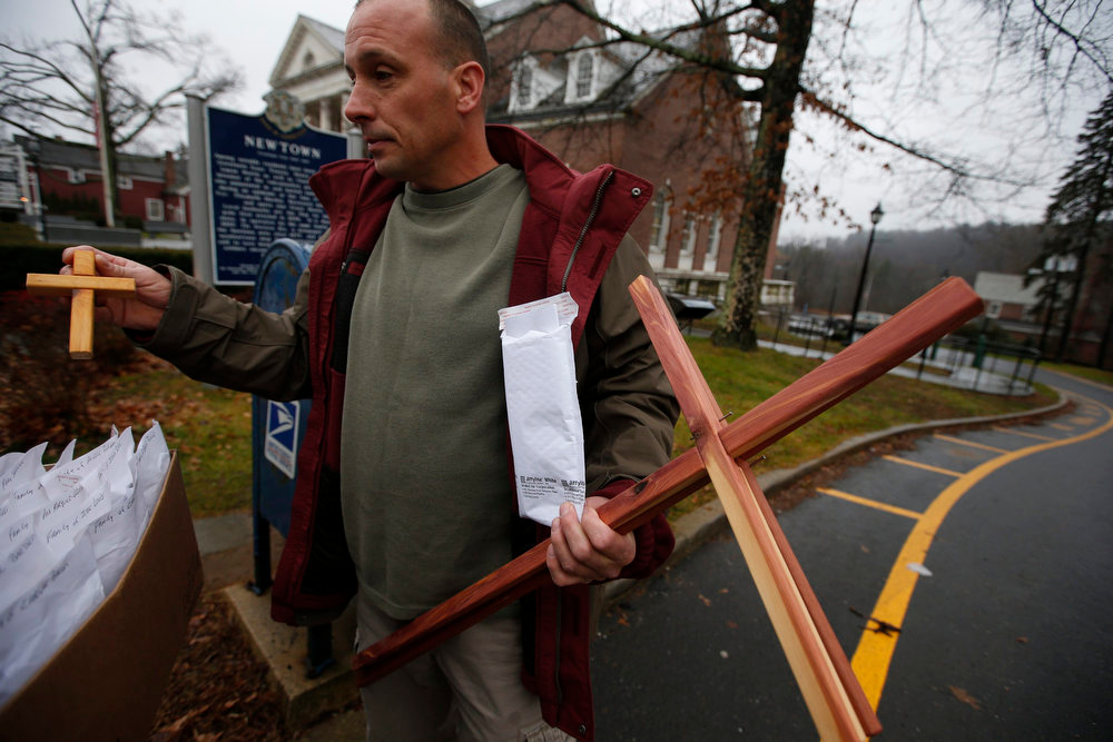 Description of . Mike Tadry from the New Harvest Christian Church of Newburgh, New York, carries wooden crosses he made to give to family members and loved ones of victims of the Sandy Hook elementary school shooting in Newtown, Connecticut, December 17,  2012. Tardy was delivering the crosses he made himself to the the funeral home in Newtown which will hold the funeral on Monday for six-year-old Jack Pinto, one of the 20 school children killed in the December 14 shootings.  REUTERS/Mike Segar
