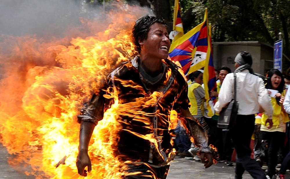 Description of . Tibetan exile Jamphel Yeshi, 27, runs as he is engulfed in flames after he set himself on fire during a protest in New Delhi on March 26, 2012.  A Tibetan exile set himself on fire on Monday during a rally in New Delhi to protest against an upcoming visit to India by Chinese President Hu Jintao, police said. AFP PHOTO/STmSTRDEL/AFP/Getty Images
